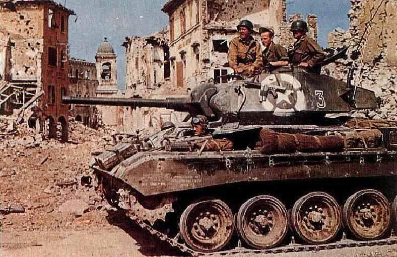 1st armored division passes through ruins of a town south of Bologna, Italy