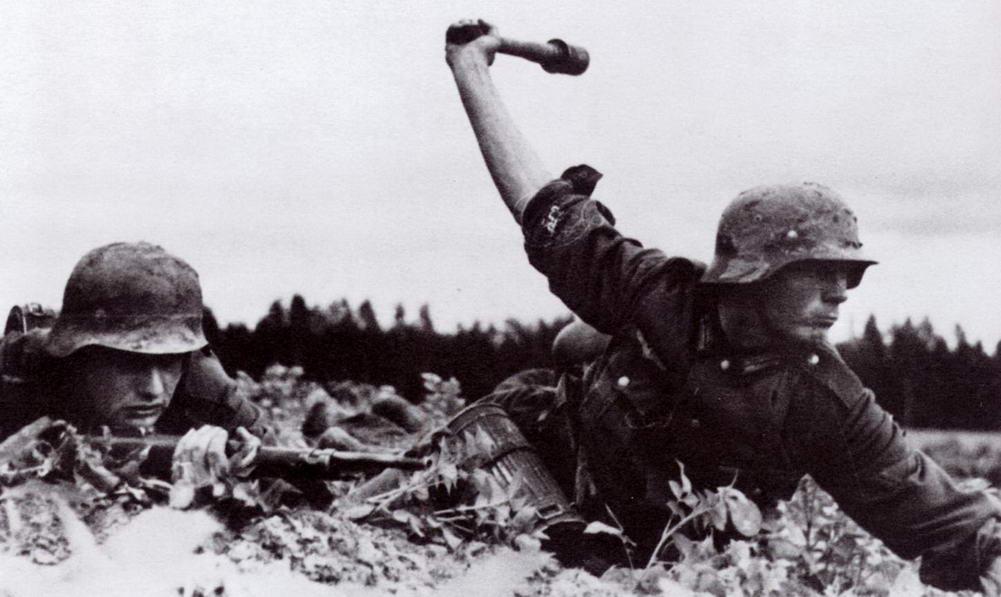 German Soldier Throws Stick Grenade. Deutsche Heer Obergefreiter (German Army Senior Lance-Corporal) prepares to throw a Model 24 Stielhandgranate (Stick Hand Grenade) ww2